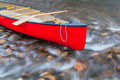 red canoe on a shallow river - PhotoDune Item for Sale