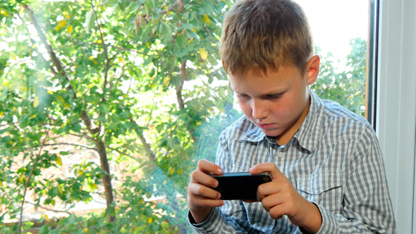 Boy Sitting By A Window Using His Smartphone