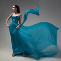 Fashion Woman In Fluttering Blue Dress. Gray Background. - PhotoDune Item for Sale