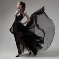 Fashion Woman In Fluttering Black Dress. Gray Background. - PhotoDune Item for Sale