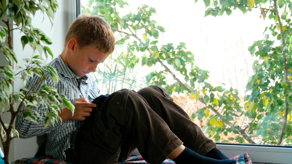 Boy Sitting By A Window Using His Tablet 2