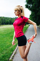 Female runner stretching her body before a park marathon - PhotoDune Item for Sale