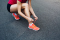 Female runner lacing up her shoes on the trail - PhotoDune Item for Sale