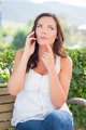 Attractive Contemplative Young Adult Female Talking on Cell Phone Outdoors on Bench. - PhotoDune Item for Sale