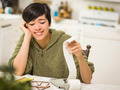 Multi-ethnic Young Woman Relieved and Smiling Over Financial Calculations in Her Kitchen. - PhotoDune Item for Sale