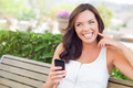 Attractive Smiling Young Adult Female Texting on Cell Phone Outdoors on a Bench. - PhotoDune Item for Sale