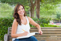 Attractive Young Adult Female Student on Bench Outdoors with Books and Pencil. - PhotoDune Item for Sale