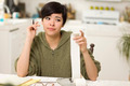 Multi-ethnic Young Woman Agonizing Over Financial Calculations in Her Kitchen. - PhotoDune Item for Sale