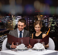 smiling couple with menus at restaurant - PhotoDune Item for Sale