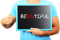 Man holding blackboard in hands and pointing the word BEYOUTIFUL - PhotoDune Item for Sale