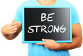Man holding blackboard in hands and pointing the word BE STRONG - PhotoDune Item for Sale