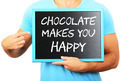 Man holding blackboard in hands and pointing the word CHOCOLATE - PhotoDune Item for Sale