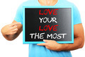 Man holding blackboard in hands and pointing the word LOVE YOUR - PhotoDune Item for Sale
