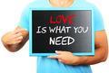 Man holding blackboard in hands and pointing the word LOVE IS WH - PhotoDune Item for Sale