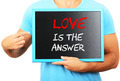 Man holding blackboard in hands and pointing the word LOVE IS TH - PhotoDune Item for Sale