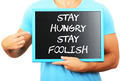 Man holding blackboard in hands and pointing the word STAY HUNGR - PhotoDune Item for Sale