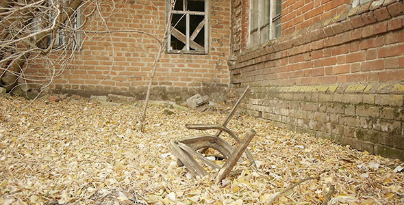 Broken Chair And Abandoned Red Brick Building