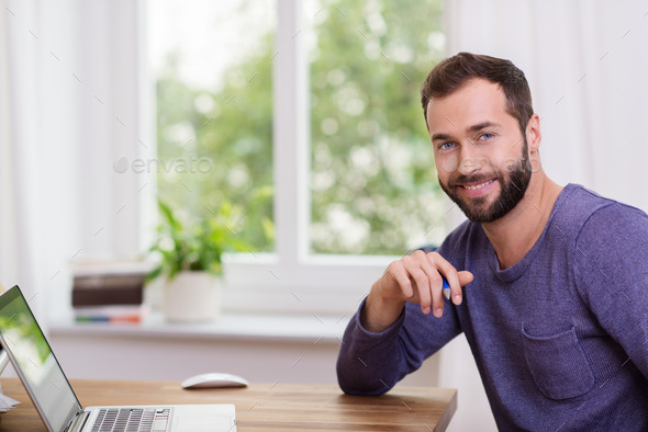 Good-looking bearded man in a home office