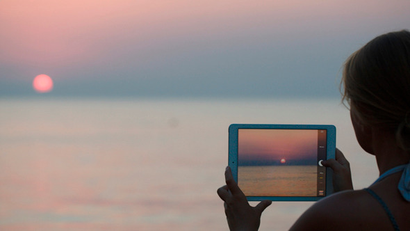Woman Making Photo Of Sunset Using Tablet Pc