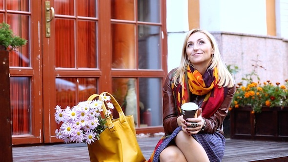 Woman Waiting On The Street Drinking Coffee