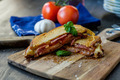 Grilled sandwich with some basil and tomatoes in the background - PhotoDune Item for Sale