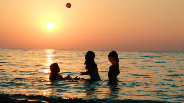 Girls Playing With Ball In Sea At Sunset