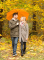 smiling couple with umbrella in autumn park - PhotoDune Item for Sale