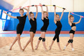 Young female gymnasts making bow with Indian clubs - PhotoDune Item for Sale