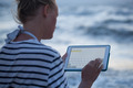 Woman typing on tablet PC by sea - PhotoDune Item for Sale