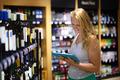 Woman choosing wine using pad - PhotoDune Item for Sale