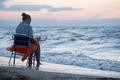 Woman sitting on chair by sea and using pad - PhotoDune Item for Sale