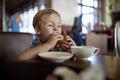 Little boy having sandwich in a cafe - PhotoDune Item for Sale