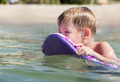 Little boy swimming on board near the beach - PhotoDune Item for Sale