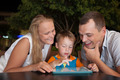 Family of three with pad in outdoor cafe - PhotoDune Item for Sale