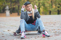 Woman with a cute smile sitting on skate board - PhotoDune Item for Sale