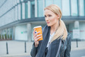 Attractive blond woman standing drinking coffee - PhotoDune Item for Sale