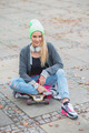 Woman in Trendy Attire Sitting Over Skateboard - PhotoDune Item for Sale