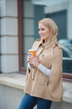Smiling blond woman pausing for a mug of coffee - PhotoDune Item for Sale