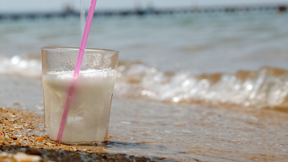 Pouring Fizzy Drink Into Glass On The Sand