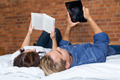 Couples Lying on Bed with Book and Tablet - PhotoDune Item for Sale