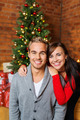 Smiling Young Couple in Front Christmas Tree - PhotoDune Item for Sale