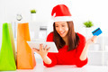 happy young woman holding credit card with tablet . Christmas shopping concept. - PhotoDune Item for Sale