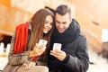 Romantic couple using smart phones during autumn walk - PhotoDune Item for Sale
