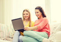 two smiling teenage girls with laptop at home - PhotoDune Item for Sale