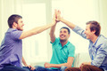 smiling male friends giving high five at home - PhotoDune Item for Sale