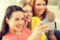 smiling teenage girls with smartphone at home - PhotoDune Item for Sale