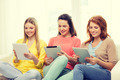 three smiling teenage girls with tablet pc at home - PhotoDune Item for Sale