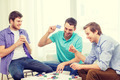 happy three male friends playing poker at home - PhotoDune Item for Sale