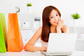 happy young asian woman using a laptop with bags. shopping on line concept - PhotoDune Item for Sale