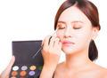 Makeup artist applying colorful eyeshadow on model's eye with a eyeshadow palettes - PhotoDune Item for Sale